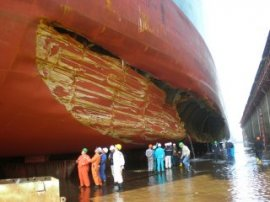 People observe a big tanker with a giant gash with its hull in dry-dock.