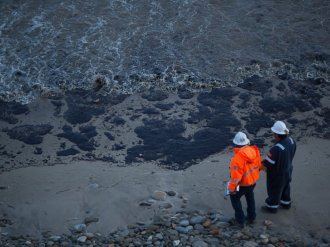 PHOTO: Officials walk along an the oil-covered coastline on 19,  2015 north of Goleta,  Calif.