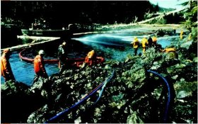 Workers in lime coats standing on rugged coastline utilizing liquid hoses to clean within the oil spill from the Exxon Valdez. (Due To Richard Stapleton. Reproduced by authorization.)